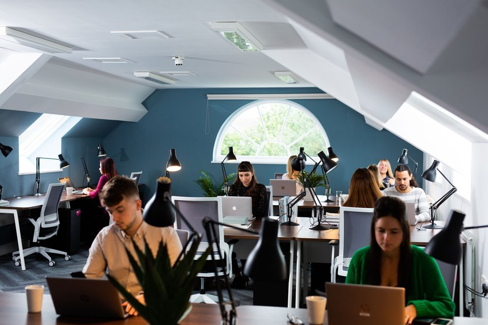 Group of people working on laptops in an office space with turquoise walls and a white ceiling