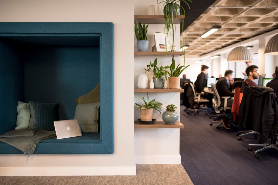 Office space with a comfy seating section in the center surrounded by people sat a office desks working on laptops