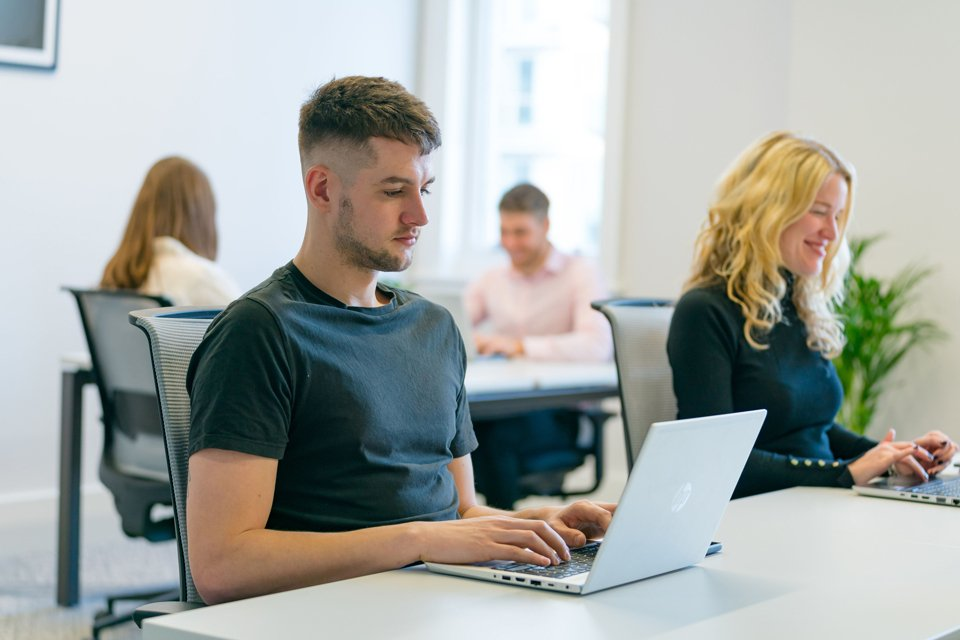 Man and a woman in the foreground sat at a white desk working on laptops.