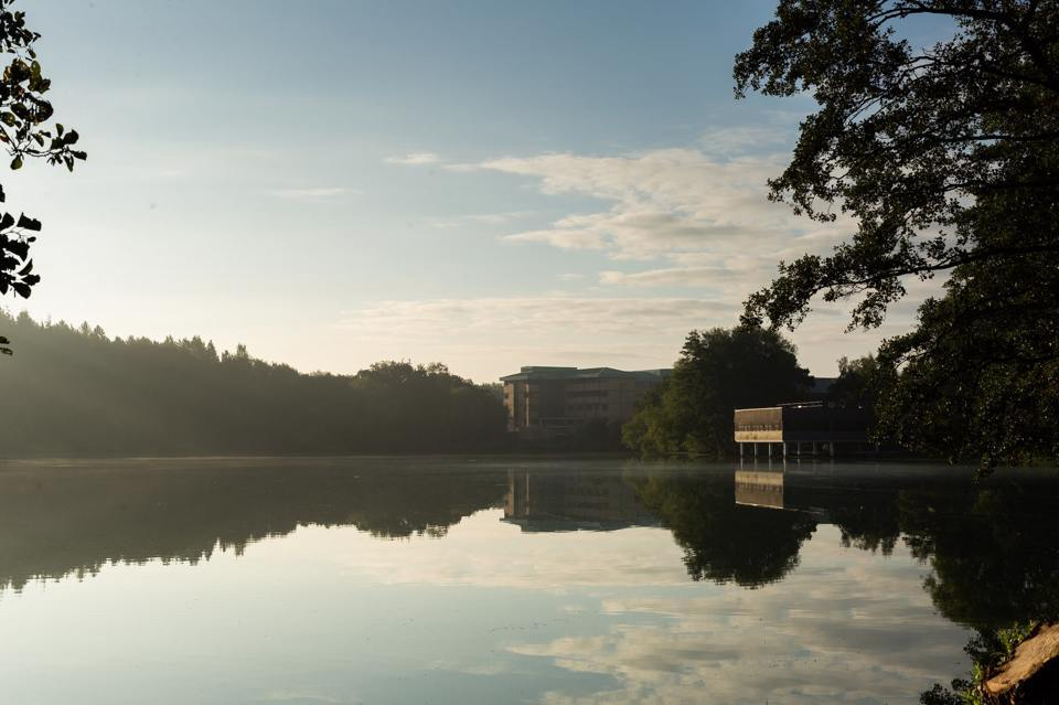 The Mere river overlooking the Alderley Park building surrounded in clear blue sky and plantation