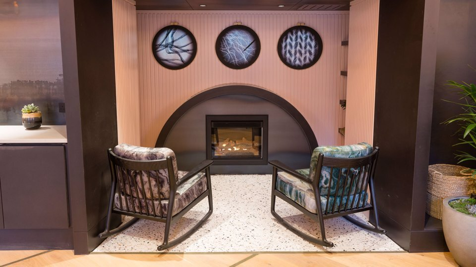 2 rocking chairs in front of a fireplace in a breakout space