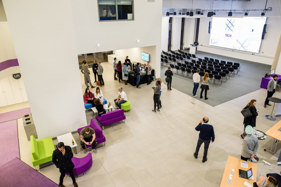 An aerial view of one of Innovation Birmingham's meeting spaces showing people stood talking, with chairs set out in a conference layout with a big screen projector.