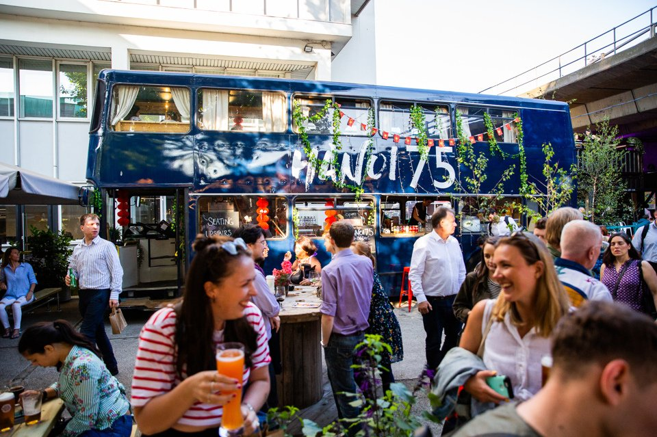 Groups of people socialising at different tables in a beer garden near a bus converted into a bar
