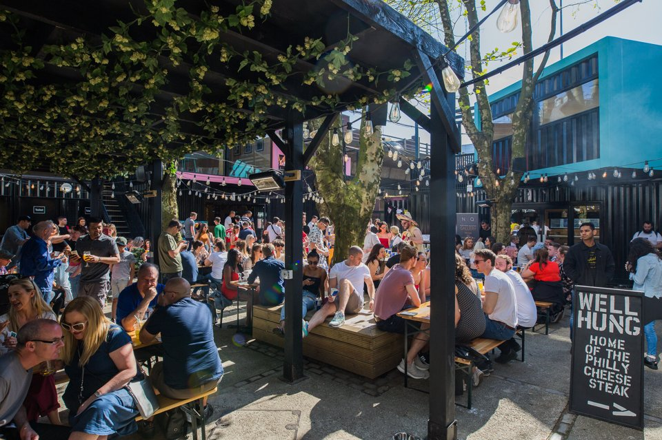 Groups of people socialising in the sun in an urban beer garden