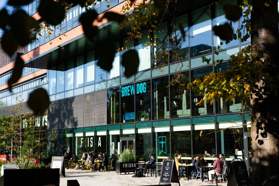 Exterior shot of people sat out Friska and BrewDog enjoying the sunshine