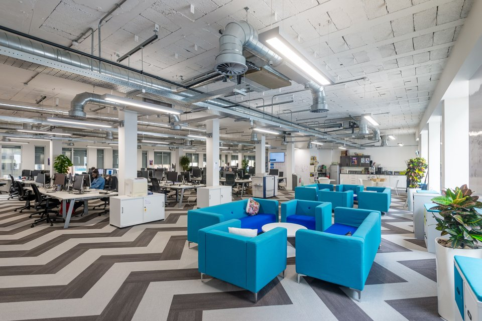 Large open office space with office desks, black and white zigzag stripe patterned carpet and blue sofas around a small white rounded desk
