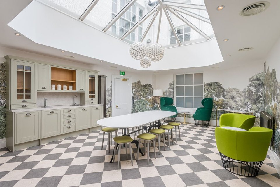Large kitchen area with black and white squre patterned flooring, green furniture and a large white, rounded table in the middle of the room