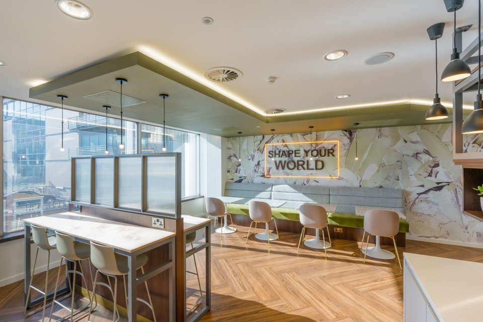 Large kitchen area containg a sign on the wall with yellow bordered lights saying 'share your world'