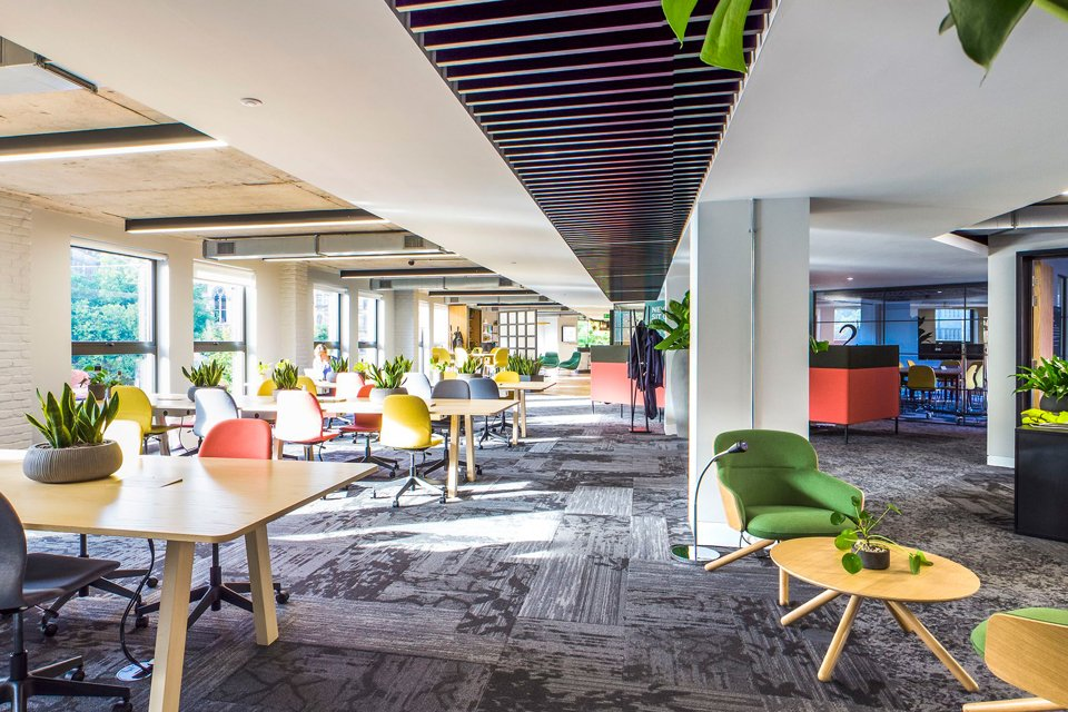 Large office space with dark patterned flooring, wooden desks and birghly coloured office chairs
