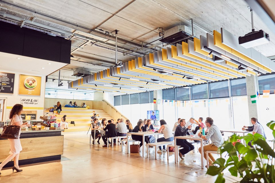 A modern design cafeteria with people eating and using laptops