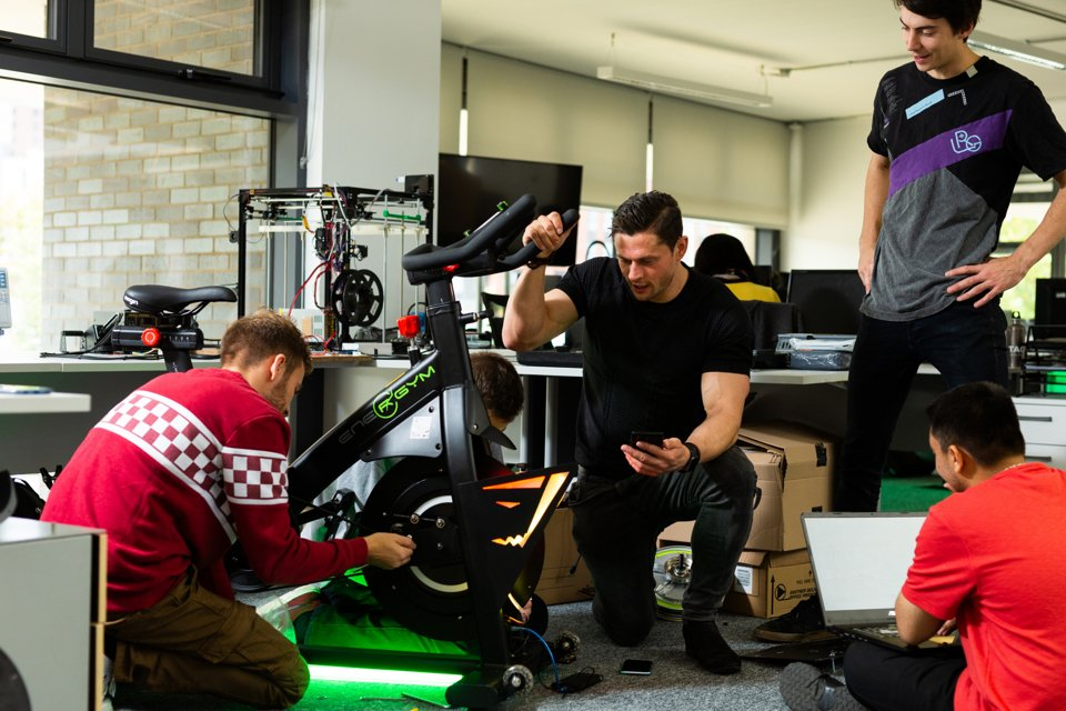 Four people using tools and computers to work on an exercise bike