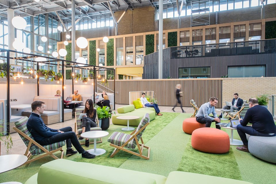 A coworking space with people sat in comfy chairs working and talking