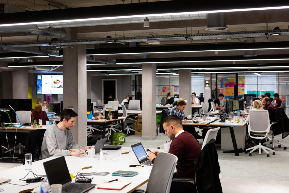 An open space office where people are working on laptops