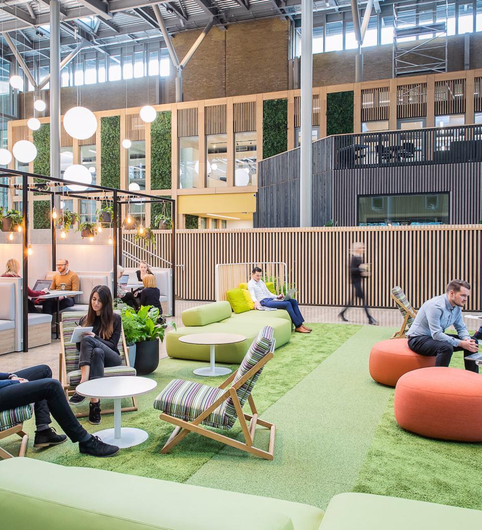 Group of people sat down enjoying the indoor open space at Alderley Park