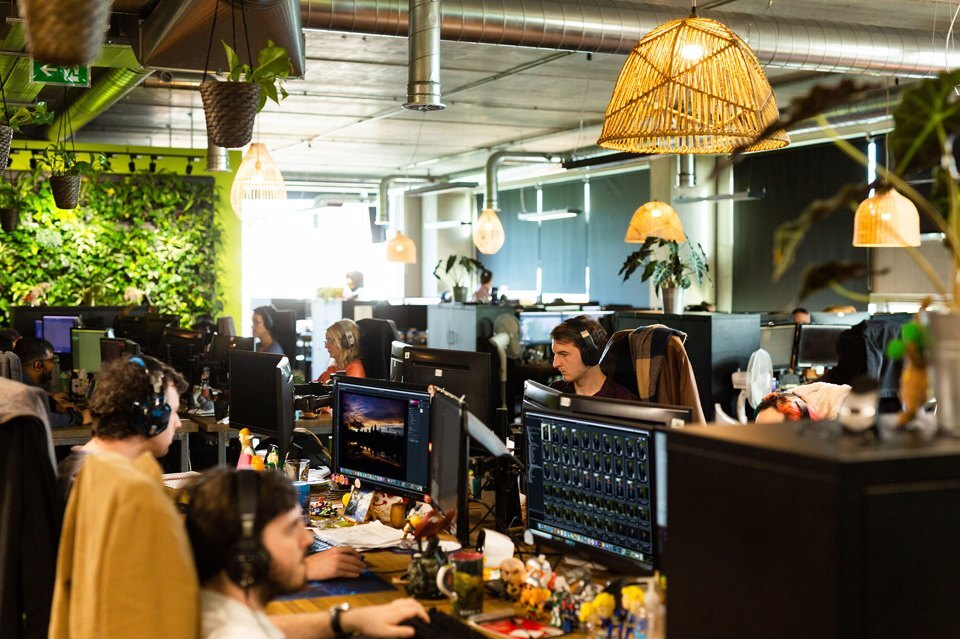 Group of people sat at a desk working on a computer while wearing headphones