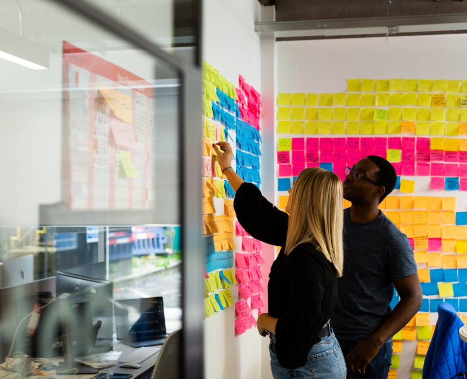 2 people having a discussion and placing sticky notes on a wall full of other notes