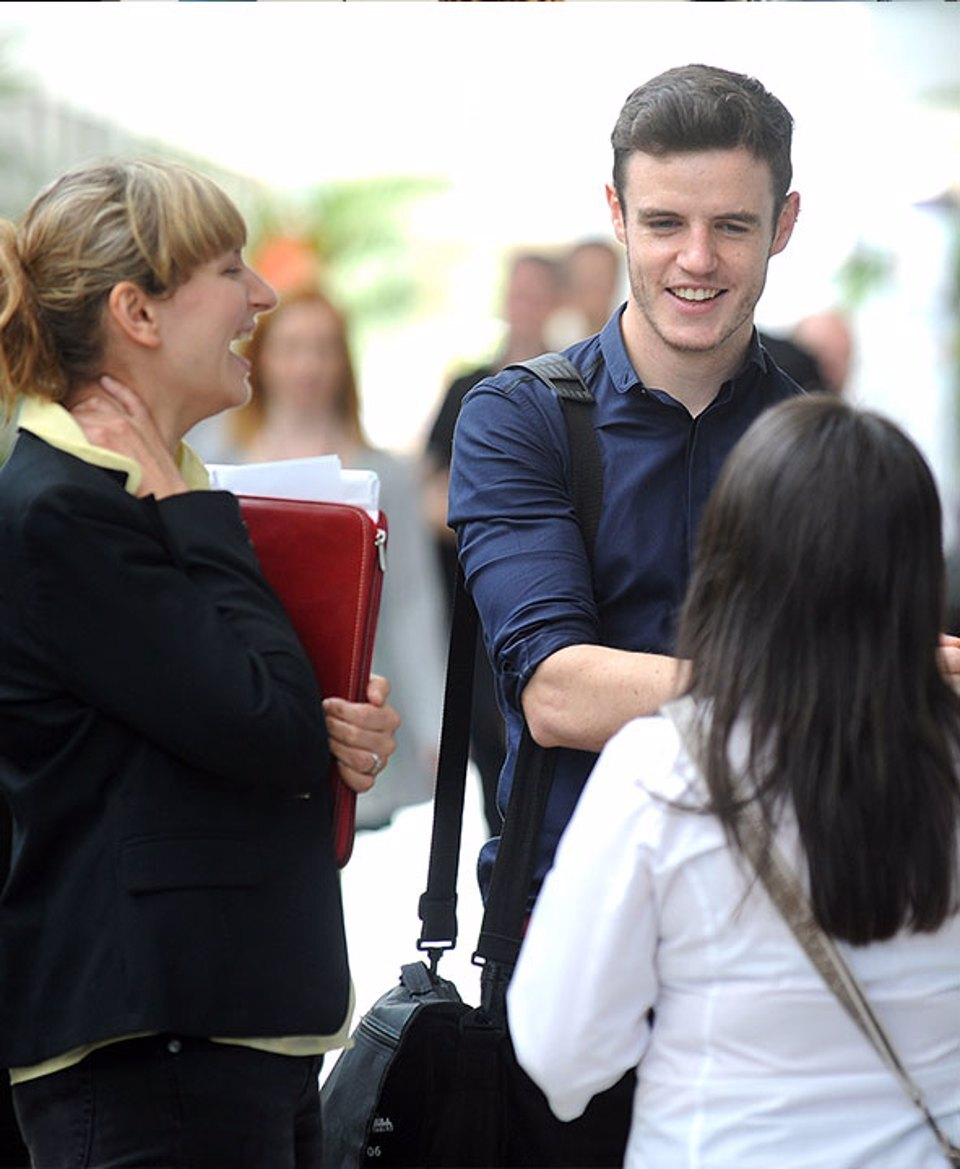 A man and two women smiling and having a discussion