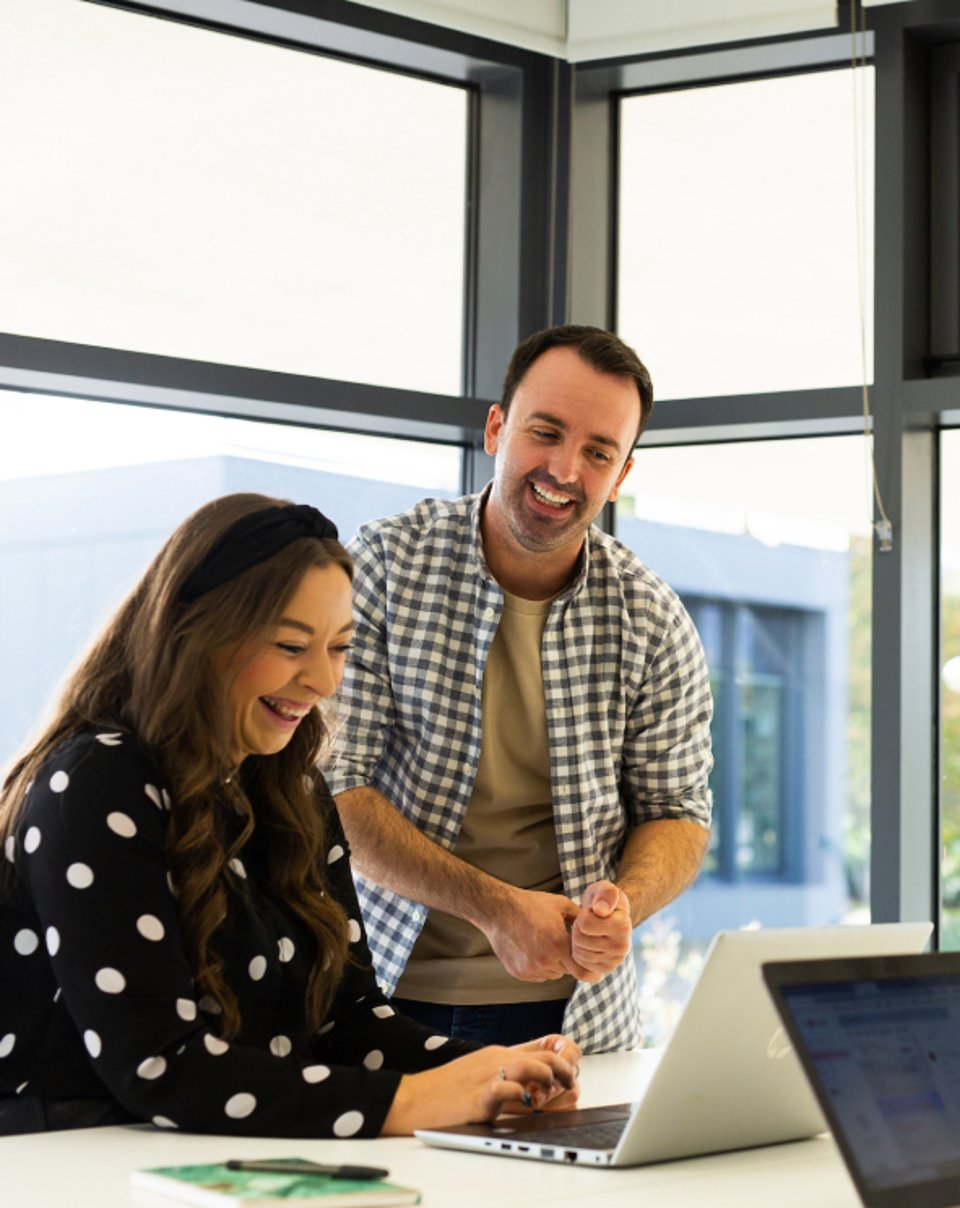 A man and a woman working on a laptop and smiling near a large window in an office