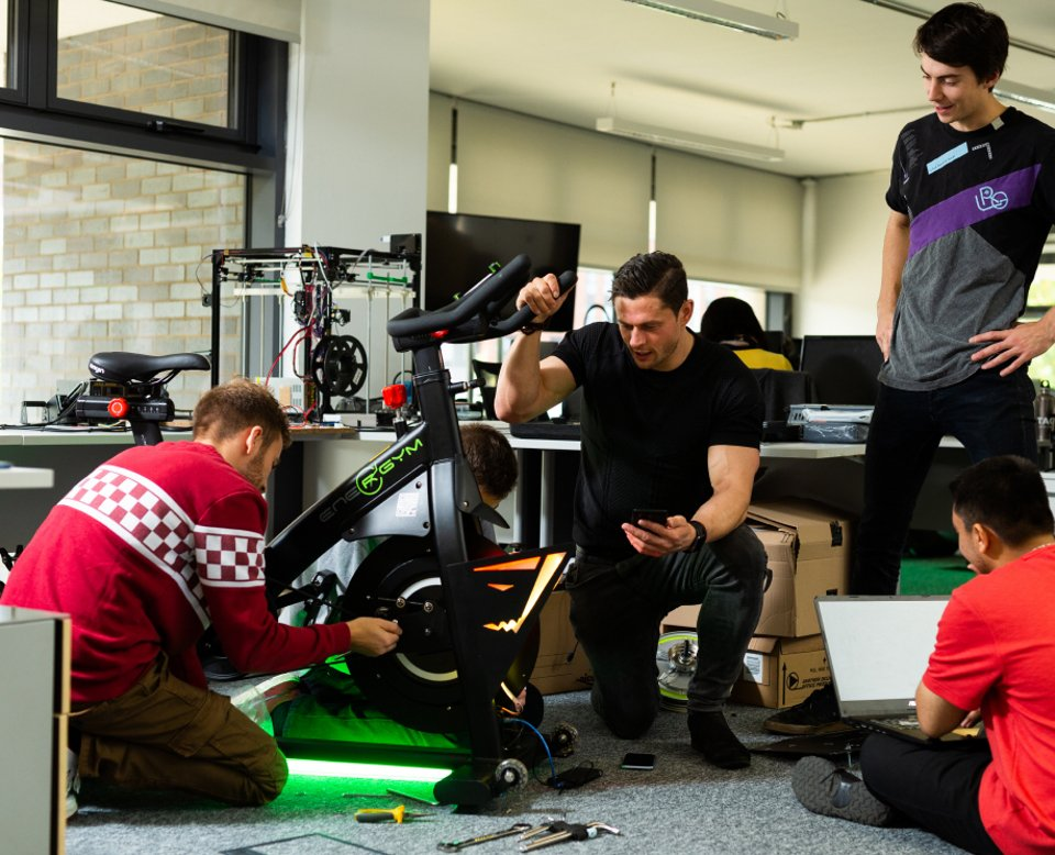 4 people working on a modified spinning bicycle with tools on the floor and looking at a laptop