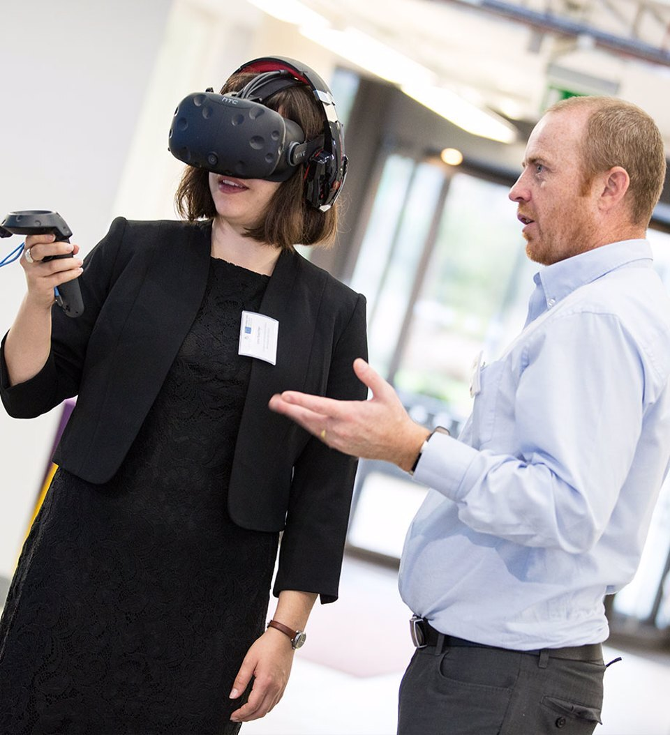 A man demonstrating to a woman wearing a VR headset