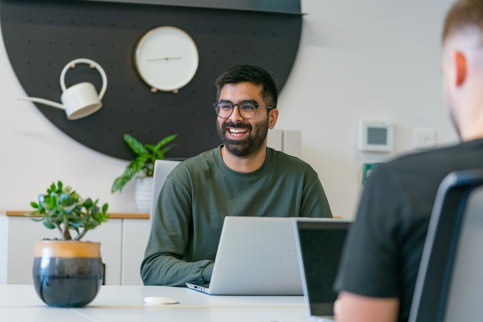 Man sat at a desk with a laptop in a white themed room and plants, looking to his right and laughing