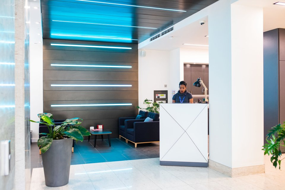 White themed reception area with comfy seating, blue striped lights on the back wall and celing and a lady stood at the reception desk
