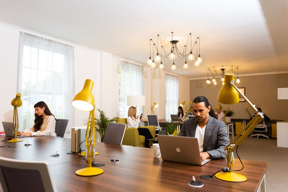 Group of people sat separately and working in office space