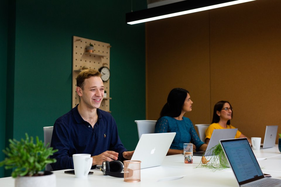 Group of people working side-by-side on laptops at office space desk
