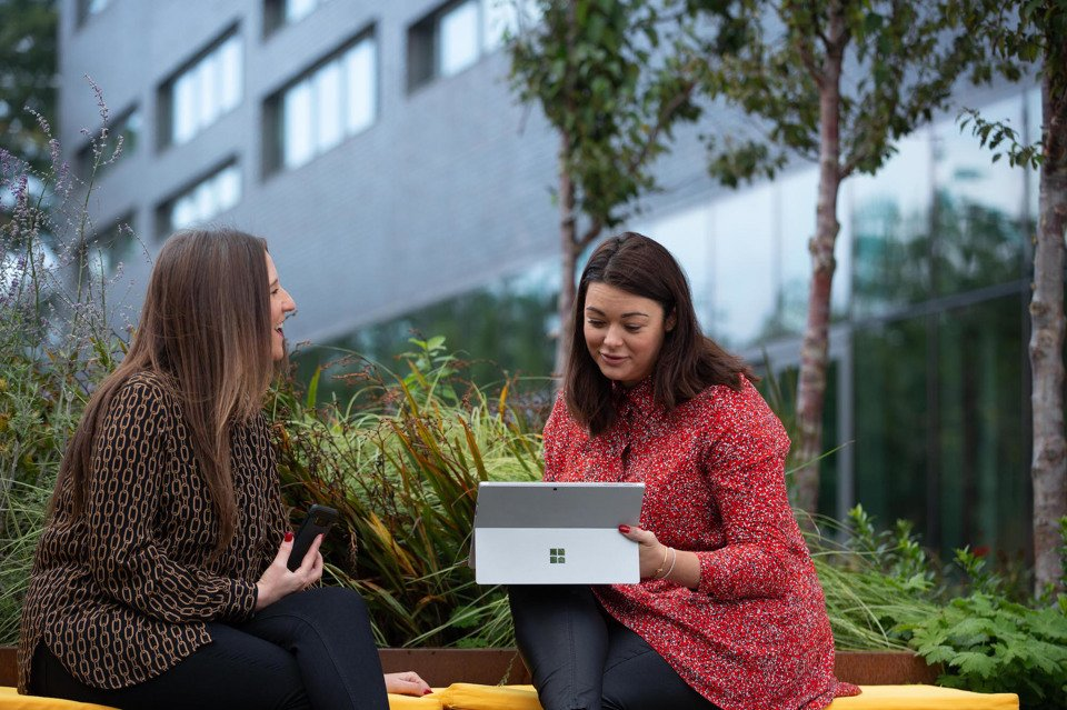 Two women sat outside the Manchester Science Park working on a laptop
