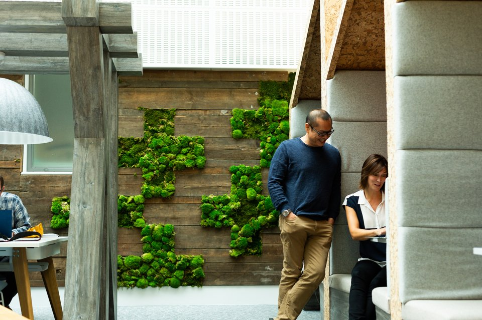 A man standing and smiling whilst talking to a woman who is sat in an urban garden meeting space