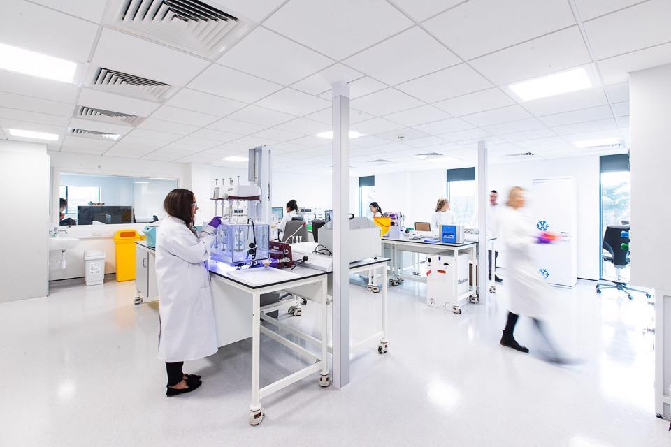 People in lab coats working in a white room at the Alderlaey Park lab space
