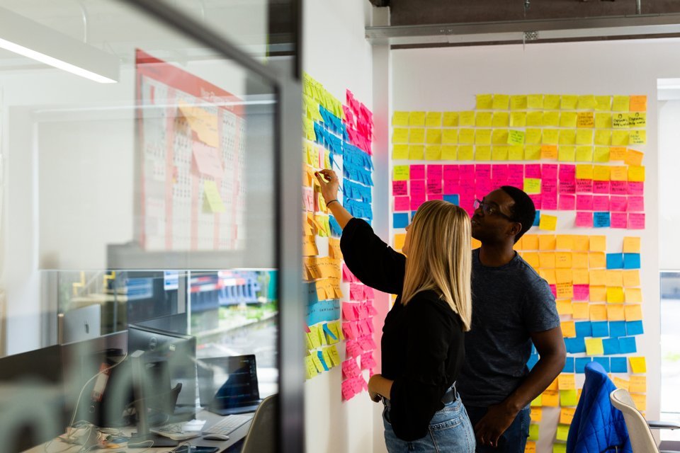 Two people collaborating at wall of post it's in a Bruntwood office