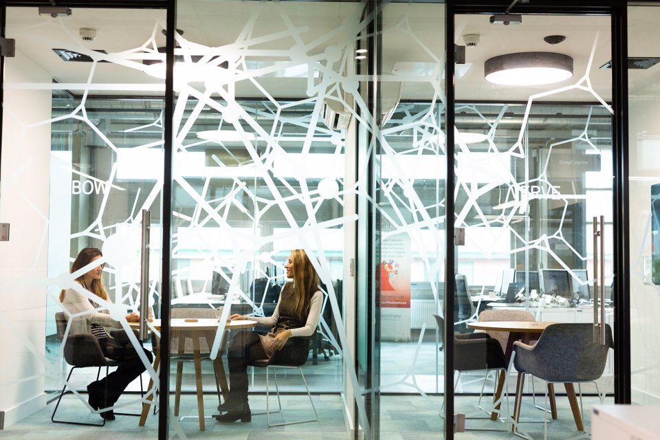 Two people sat in a meeting room behind a large glass patterned door