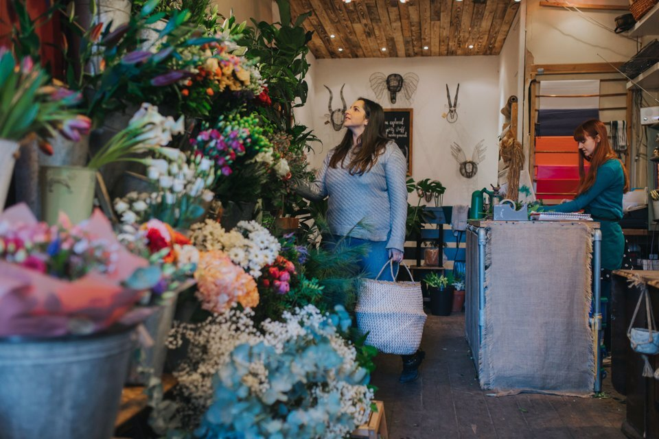 Woman carrying a bag looking at large collection of flowers to buy