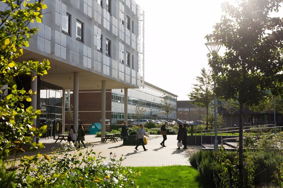 Outside look at the Innovation Birmingham Campus and surrounding park with people entering and exiting the main building