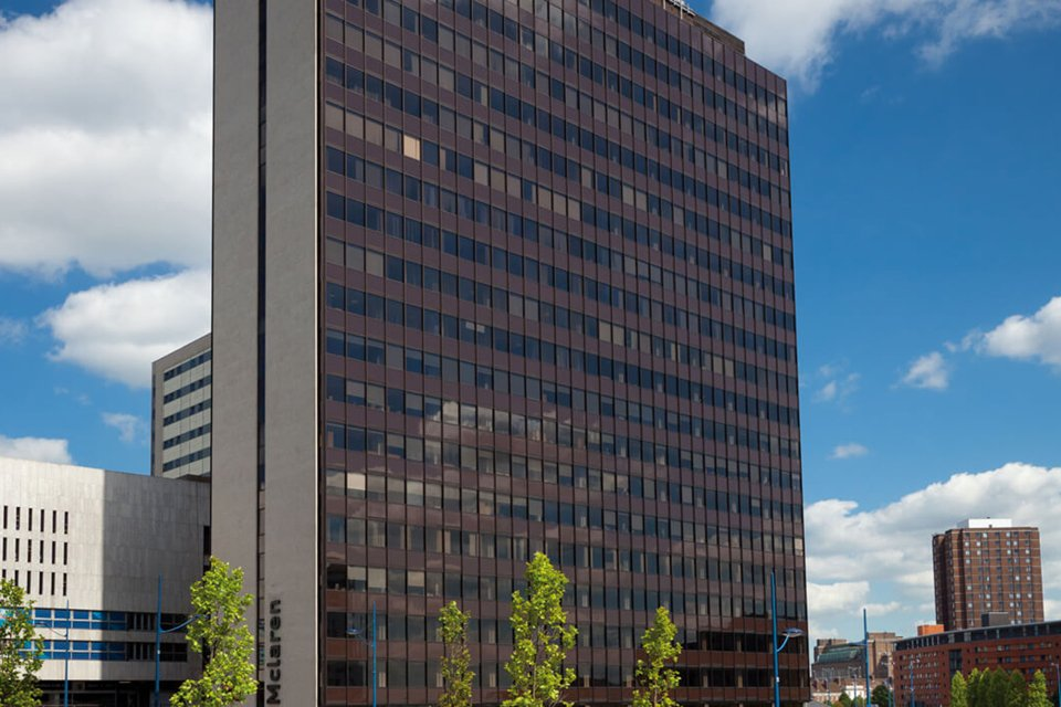 Outside look at the skyscraper like mclaren building surrounded by smaller buildings and some tress