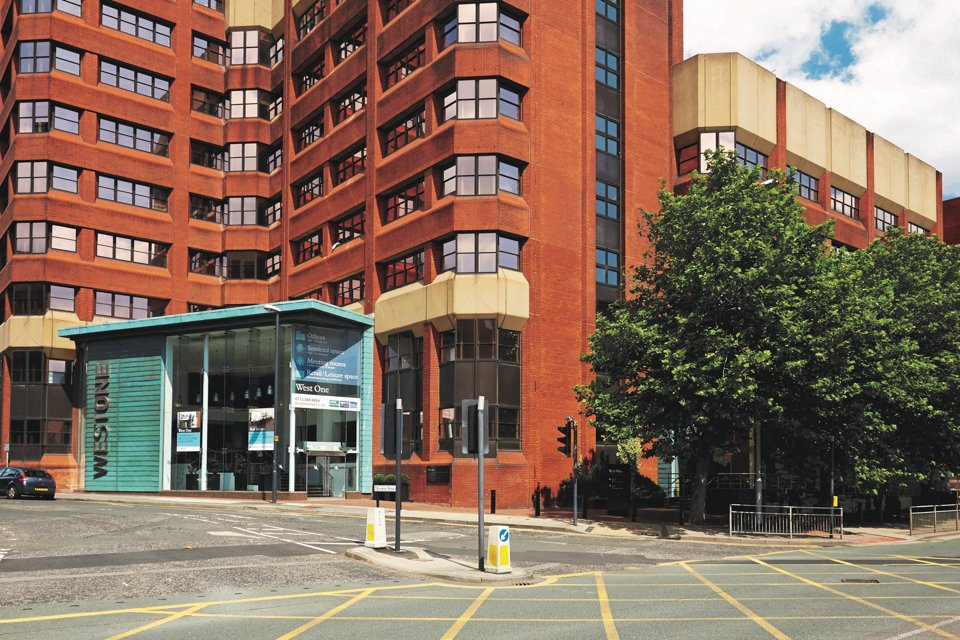 Outside look at the front of the west one building, situated next to a main road and some trees