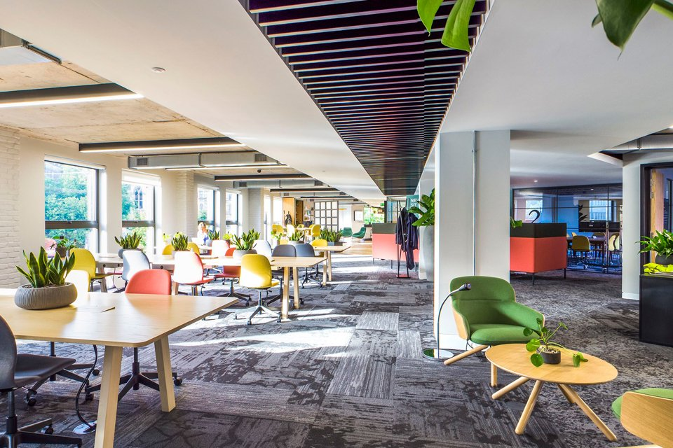 Wide and spcaious office area with brighlty coloured office chairs.