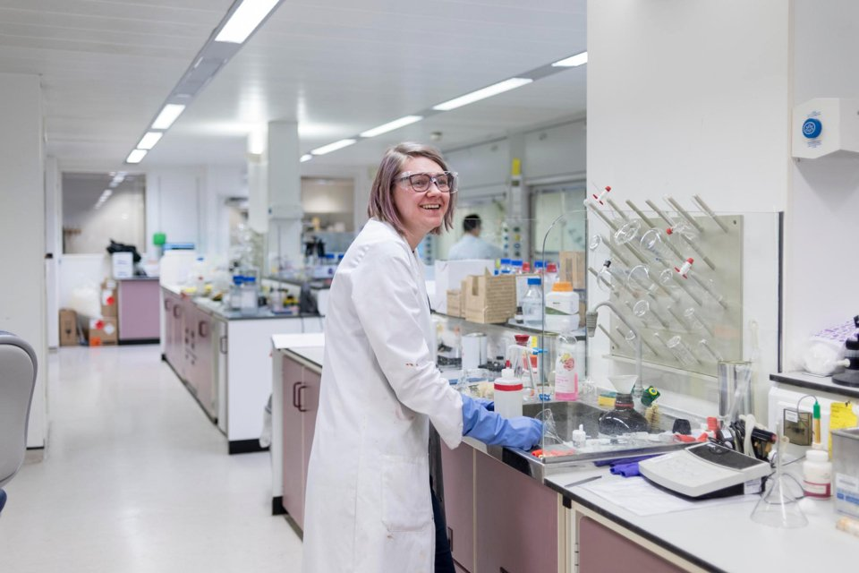 Woman in a white lab coat, wearing blue gloves and safety glasses, stood by a lab desk and smiling