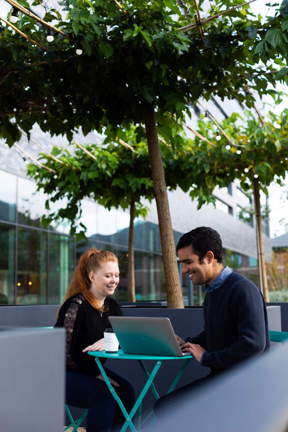 Man and a woman sat at a desk outside smiling while working on a laptop
